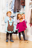 Boy fits vest and girl with sweater in store Stock Photo