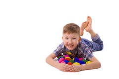Boy of five years with easter eggs lying on the floor Stock Photos
