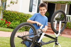 Boy fixing bike in garden Stock Photo