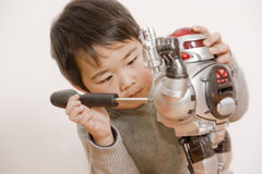 Boy fixing robot royalty free stock photos