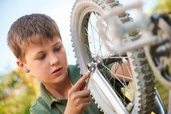 Boy Fixing Wheel Of Bike Stock Images