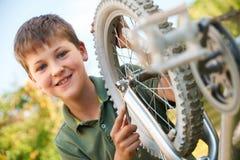 Boy Fixing Wheel Of Bike Royalty Free Stock Photo