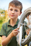Boy Fixing Wheel Of Bike Royalty Free Stock Photos