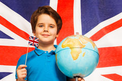 Boy with flag and globe in front of British banner Royalty Free Stock Image