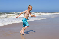 Boy fleeing a wave at sandy beach Royalty Free Stock Photos