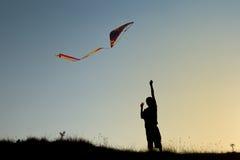 A boy flies a kite Stock Image