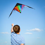 Boy flies kite into blue sky. Joy teen flies kite into blue sky, outdoor, summer Stock Image