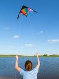 Boy flies kite into blue sky. Joy teen flies kite into blue sky, outdoor, summer Royalty Free Stock Photography
