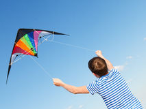 Boy flies kite into blue sky. Joy teen flies kite into blue sky, outdoor, summer Royalty Free Stock Image