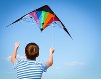 Boy flies kite into blue sky. Joy teen flies kite into blue sky, outdoor, summer Royalty Free Stock Photos
