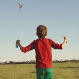 Boy flies kite into blue sky. Joy teen flies kite into blue sky, outdoor, summer Stock Photo
