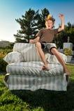 Boy flies thru air to land on chair Stock Photo