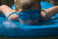 Boy on a Float. A wet boy on a blue float in the water at a pool, lake or ocean stock image