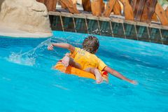Boy on float in pool Stock Images