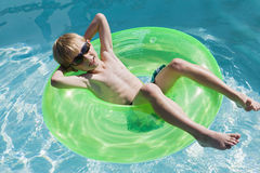 Boy On Float Tube In Swimming Pool Stock Photos