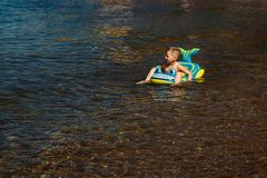 The boy floating on an inflatable baby boat royalty free stock photo