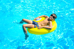 Boy floating on an inflatable circle in the pool. Royalty Free Stock Photography