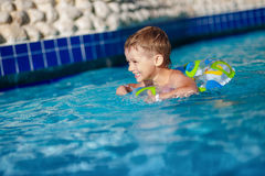 Boy floating on an inflatable circle in the pool.  swimming into resort Stock Photos