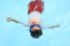 Boy Floating in Pool Stock Images
