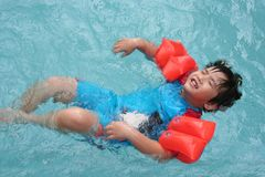 Boy floating in the pool. Boy wearing orange arm float floating in the pool Stock Image