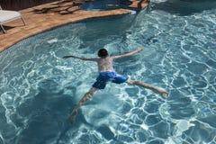 Boy floating in swimmingpool stock photo