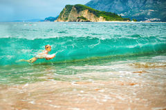Boy floating on the waves Royalty Free Stock Photos
