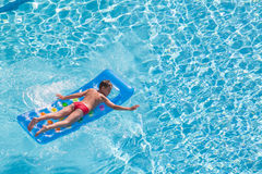 A boy floats on an inflatable colored mattress Royalty Free Stock Images