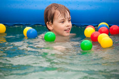 Boy floats in inflatable pool with balls Stock Image