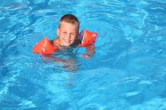 Boy floats in pool Stock Images