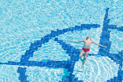 A boy floats in the pool face up Stock Photo