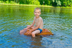 Boy floats on the river Stock Photography