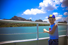 Boy floats on ship near island at background of Royalty Free Stock Photography
