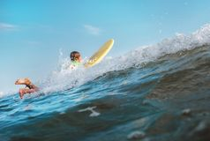 Boy floats on surf board over the wave crest Royalty Free Stock Photography