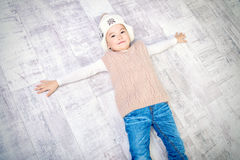 Boy on a floor. Cute little boy in winter clothes lying on a floor. Kid`s fashion Stock Photos