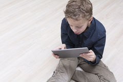 Boy on floor with tablet pc Stock Photos