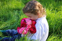 Boy with flowers. Little boy sitting in the garden smelling  a bunch of roses Stock Photography