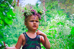 The boy in flowers chaplet after rain. The young boy in flowers chaplet after rain Royalty Free Stock Photos