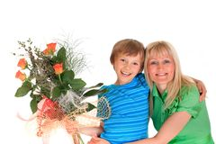 Boy with flowers for mom. Horizontal studio portrait of a smiling young boy with his mother, his arm around her shoulders, holding a peach rose bouquet for her Stock Image