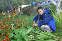 Boy with flowers outdoors Royalty Free Stock Photos