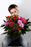 Boy with flowers. Sad boy waiting with a beautiful bunch of flowers to say i am sorry stock photos