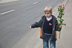 A boy with flowers stops the car Royalty Free Stock Image