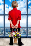 Boy with flowers waiting for her mother.Looking in the window. Beautiful boy with flowers for mom.Stylish boy royalty free stock photo