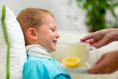 Boy with flu measuring temperature by thermometer at home Stock Photos