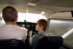 Boy is flying aircraft assisted by a trainer Royalty Free Stock Image