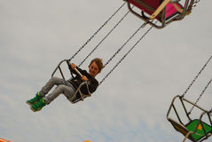 Boy on flying carrousel. A boy sits on a flying carrousel at the local autumn fair Stock Image