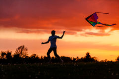 Boy flying his kite against a spectacular sunset Royalty Free Stock Photos