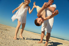 Boy flying on his parent 's hands. At beach Royalty Free Stock Image
