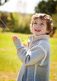 Boy flying a kite. Child holding a kite sting and looking into the sky Stock Photo