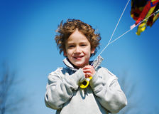 Boy flying a kite. Young boy smiling and holding a flying kite against a bright blue sky Royalty Free Stock Photos