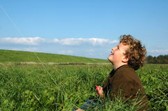 Boy Flying Kite. Boy (7) sitting in grass holding and looking at a kite high in the air Royalty Free Stock Photography